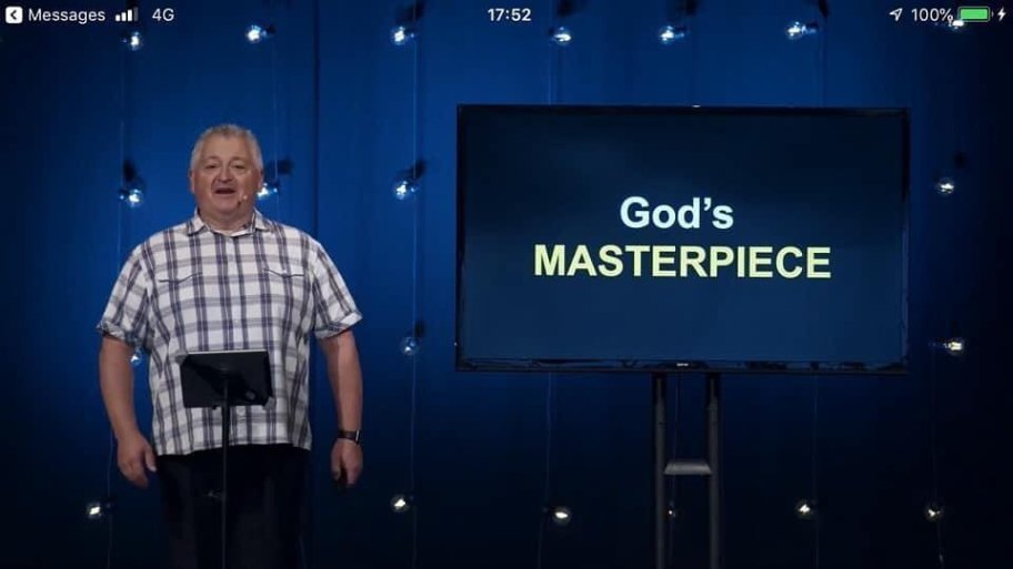 Mike Groom standing with God's Masterpiece title displayed on a TV