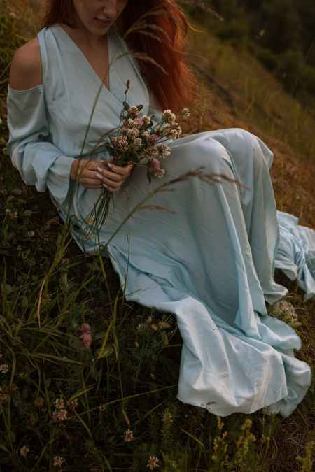 person in a dress sitting on grass holding bouquet of flowers