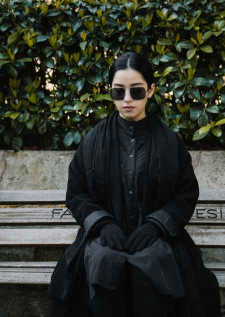 quiet woman in sunglasses and black outfit sitting on bench
