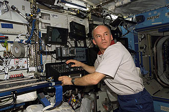 ISS013-E-40003 -- Astronaut Jeffrey Williams works the controls of the Canadarm2