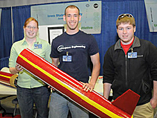 Three students holding part of a rocket
