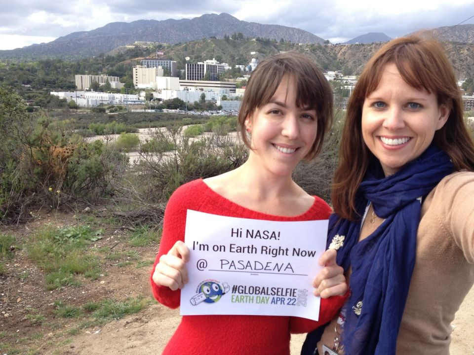 Two people pose with a NASA #GlobalSelfie sign