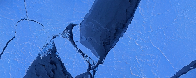 dark blue river of ocean between two pale blue shores of ice,