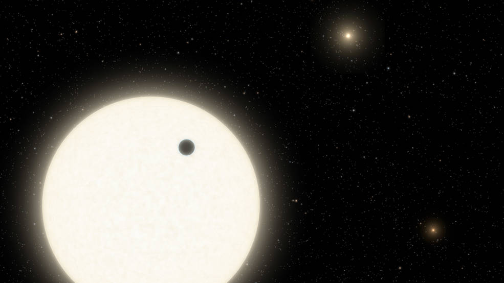 Illustration showing the planet KOI-5Ab transiting across the face of a Sun-like star, which is part of a triple-star system