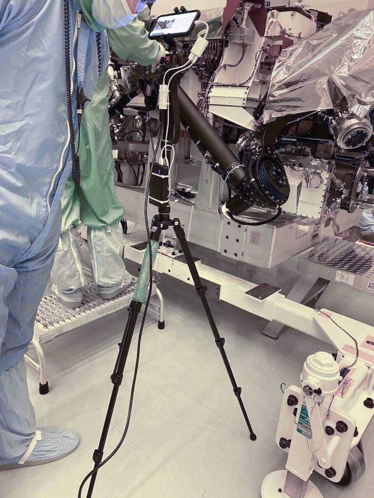 A technician points a smartphone camera at NASA's Perseverance rover during an inspection