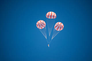 An Orion test article descends under three main parachutes