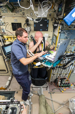 astronaut Scott Kelly strapped into ultrasound gear, which is operated by cosmonaut Sergey Volkov