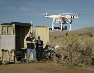 Photograph of drone being flown with operator and observers slightly out-of-focus in the background
