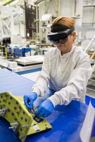 A technician wears augmented reality goggles to work on crew module hardware at NASA's Kennedy Space Center in Florida.