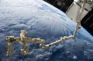 space station's robotic arm next to space-x dragon