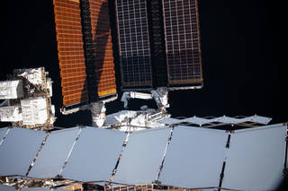 NASA astronaut Shane Kimbrough (left) and ESA (European Space Agency) astronaut Thomas Pesquet maneuver the first ISS Roll-Out Solar Array (iROSA) into place on the space station's port 6 truss structure during a spacewalk June 16, 2021.