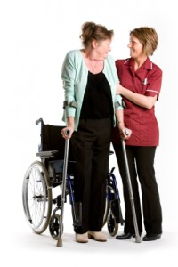 home care nurse helping patient stand from wheelchair
