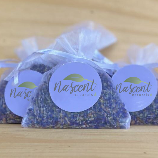 Three dried lavender sachets side by side in front of a wood background