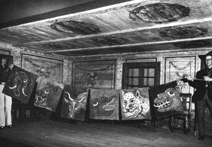 """Bilden är tagen i """"Häradssköglestugan"""", som nu står uppmonterad på länsmuseet.  Varglapparna som skänktes till Fornminnesföreningen, finns nu bevarade på Länsmuseet i Jönköping. Målningarna på lapparna är uttörda av Magnus Wikander, samme man som 1765 dekormålade kyrkan invändigt. Sannolikt gjordes dessa bägge arbeten vid samma tidpunkt. Det sista stora vargskallet i Näshult socken gick på våren 1840."""