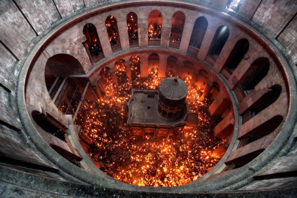 epa02699559 View looking down from the rotunda inside the Church of the Holy Sepulchre in Jerusalem that shows the Tomb of Christ as the miracle of the Holy Fire occurs on 23 Arpil 2011, the day before Easter. Eastern Orthodox Christians believe the Holy Fire, which emenates from within the Tomb of Christ and quickly spreads around the church and outside to Jerusalem and even to foreign countries, represents the flame of the Resurrection power, as well as the fire of the Burning Bush of Mount Sinai.  EPA/ABIR SULTAN ISRAEL OUT