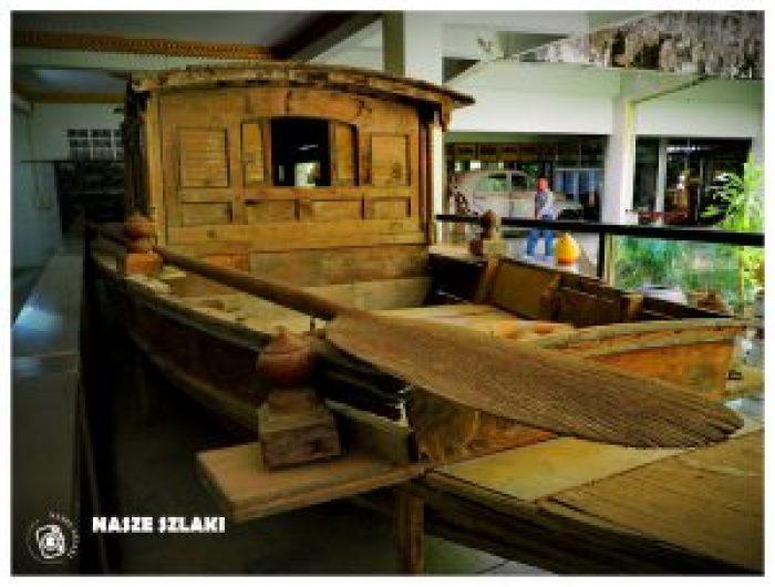 Drewniana łódź w muzeum wojny w Kanchanaburi. W tle dziedziniec muzeum i zwiedzający turyści. Atrakcja turystyczna dla podróżników