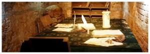 Podziemia w twierdzy Kłodzko, stół z dokumentami i monetami, półki z książkami, worki i krzesła