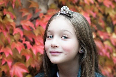 Young girl with red, autumn leave behind her and a pet geico on her head.