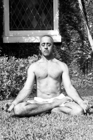 Man seated on the grass in easy pose.