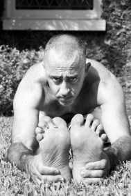 Concentrated man in Paschimottanasana on the grass in Miami.