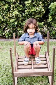 Boy with long brown hair squatting on an upside down chair.