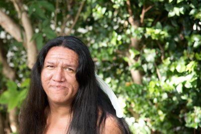 Native man with white feather in his long, dark hair gazes pensively.