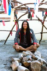 Native man sits inside a sweat lodge with Grandfather stones in front of him.