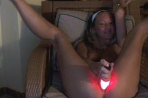 Natalie K on a chair with glowing dildo