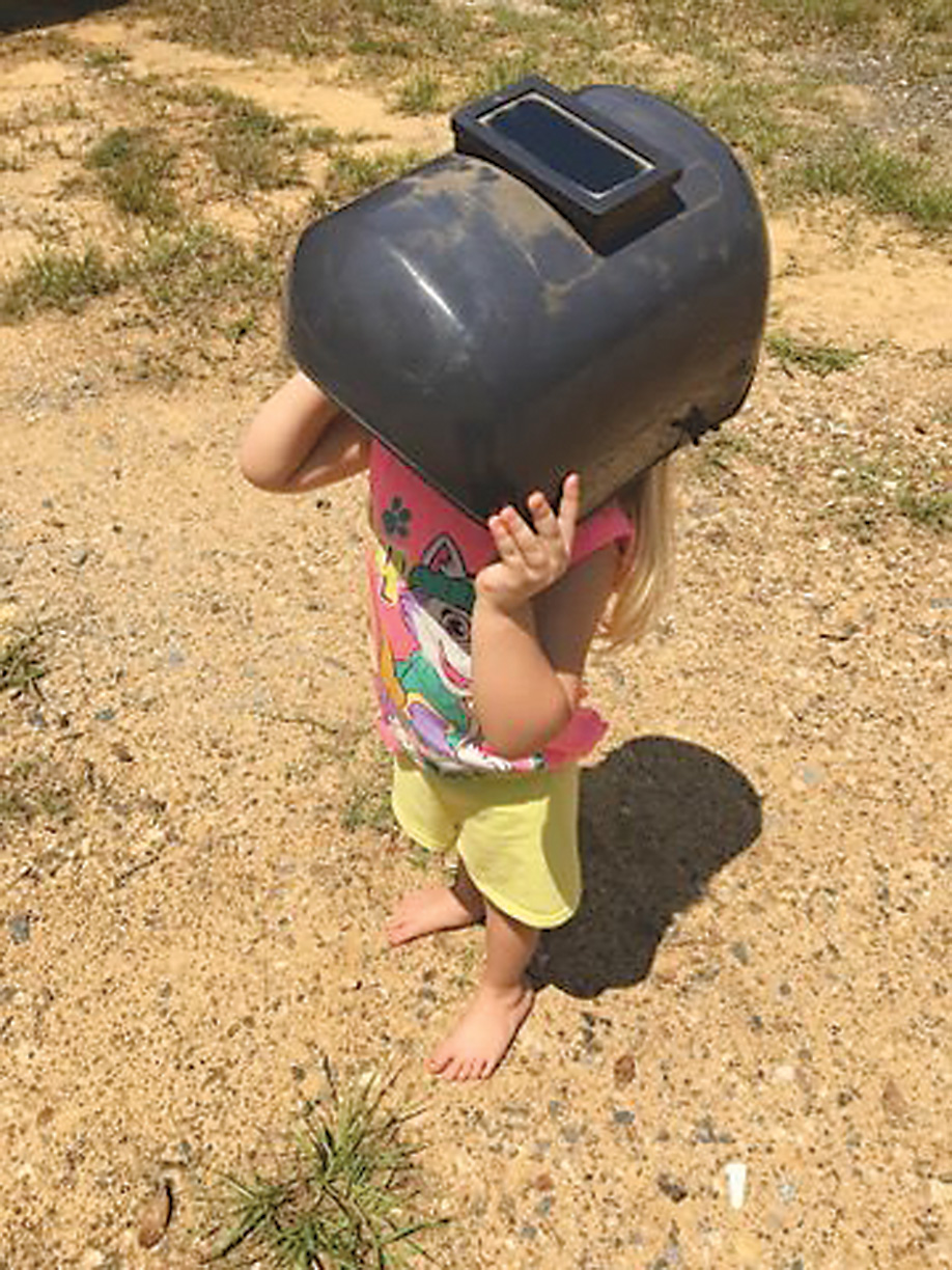 Remington Bamberg, 2, looks at the eclipse, protected by a welder's helmet.