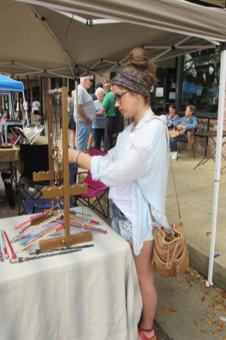 Josie Roach browses the necklaces on display at one of the art booths.
