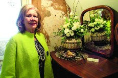 Cynthia Brown used white roses and coffee beans, placed in a vase that compliments the wall in the background.