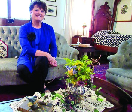 Margaret Berry primarily used roses, goldenrod, yellow daisy, a curly willow branch and accented with a cute bird nest.