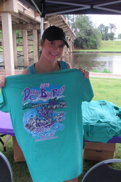 Mackenzie Panther holds up an offical 2019 Dragon Boat Races T-shirt.