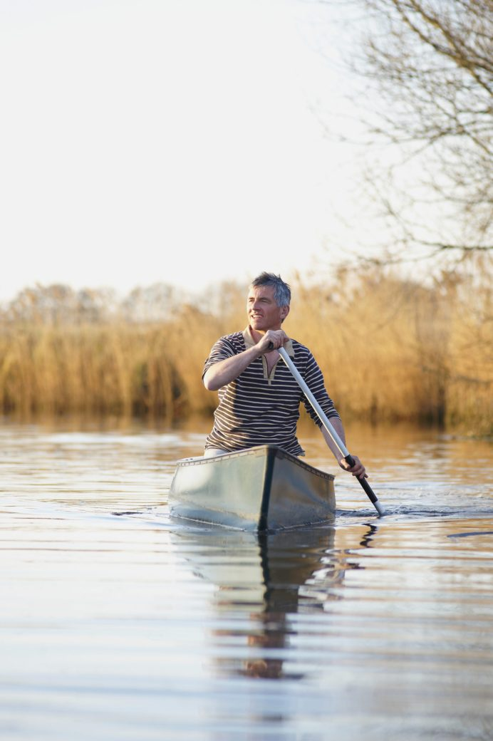 Man canoeing along river in countryside.