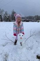 Aubree Jo Dahl and her first snowman.