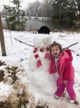 Three year old Preslee Cruse with her loving snowman.