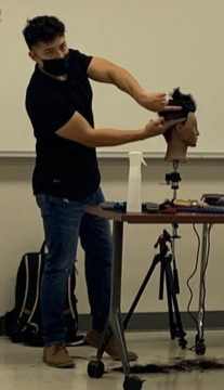Barber Jorge Arellano demonstrates his techniques on a mannequin head.