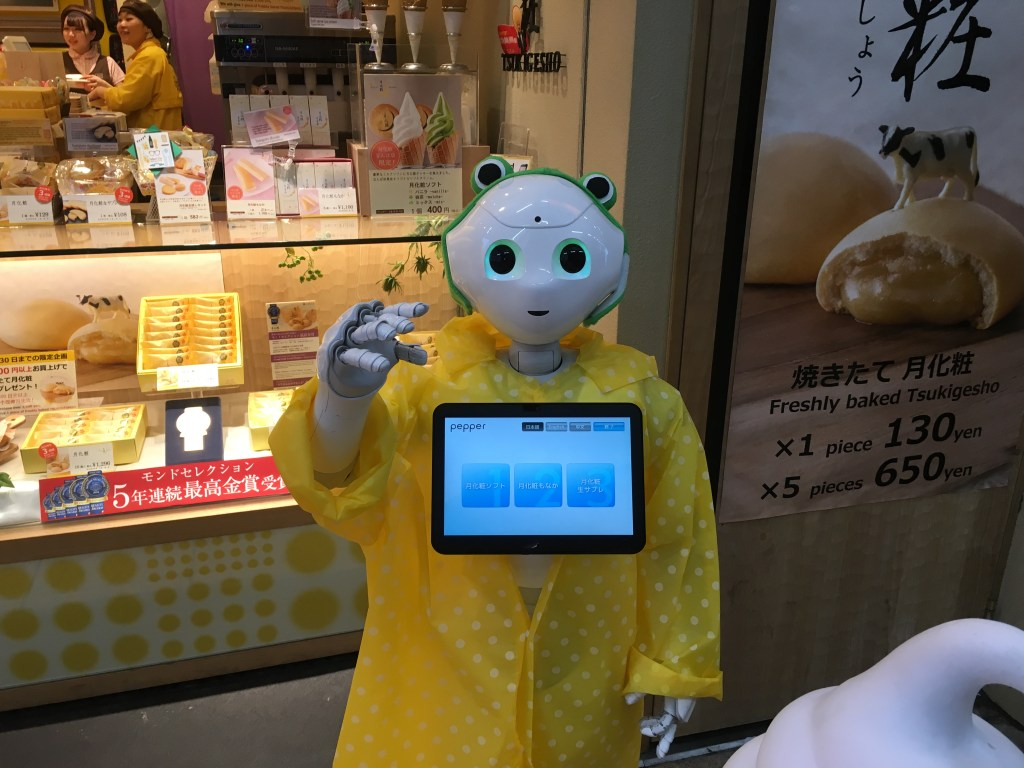A Pepper in front of a souvenir shop in Osaka on a rainy day.