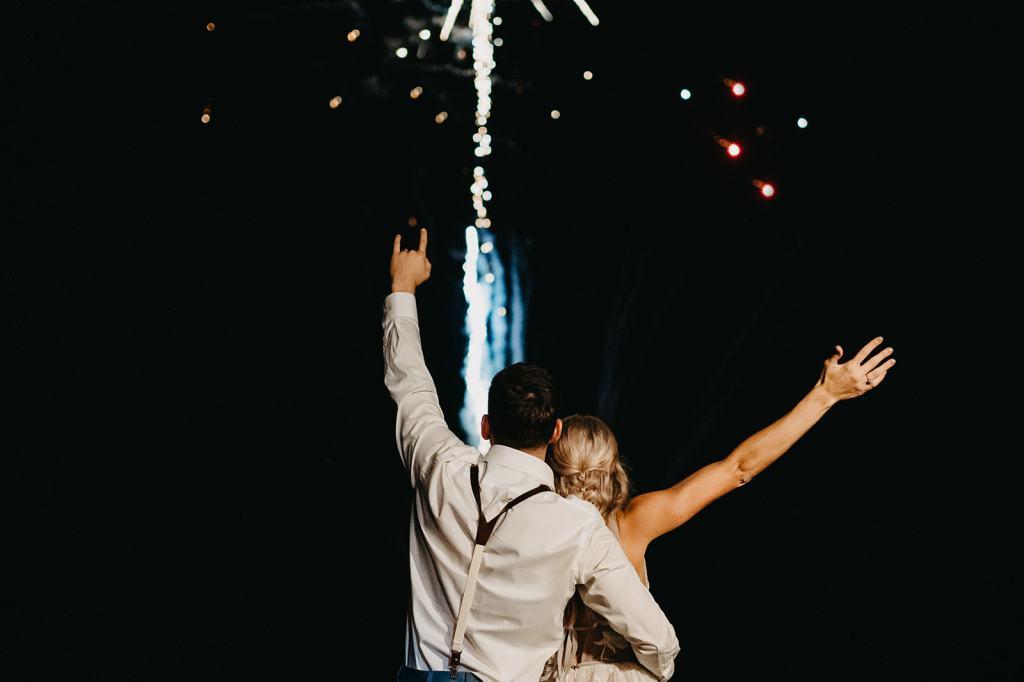 couple watches fireworks at boho wedding