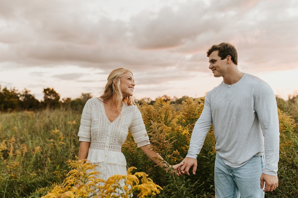 Engaged Couple holds hands in wildflower field