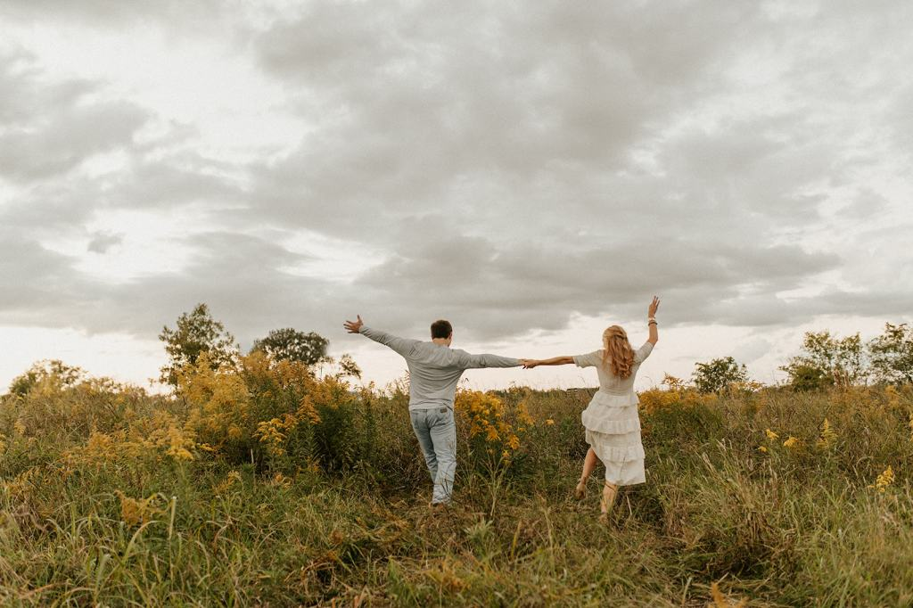 Couple runs through field at engagement session