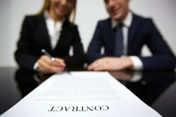 man-and-woman-signing-a-contract