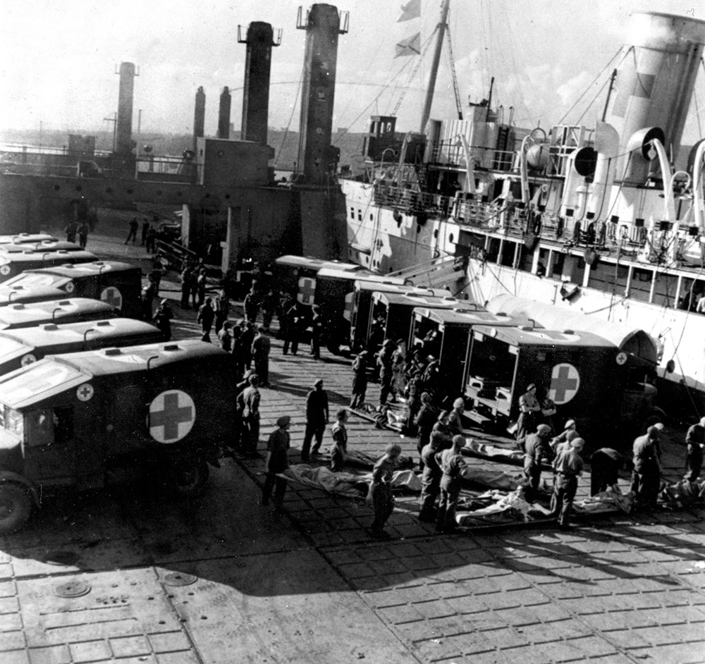 Image of a black and white photograph of casualties of the D-Day landings being loaded into vehicles at the pierheads, June 1944
