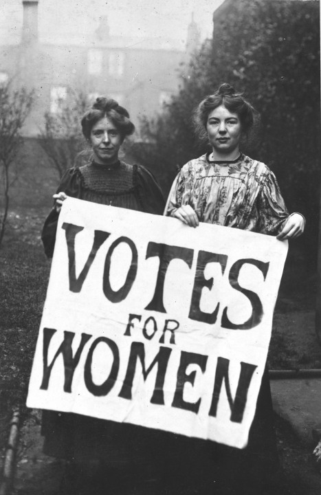 Suffragettes Annie Kenny and Christabel Pankhurst holding up a sign with 'Votes for women' written on it