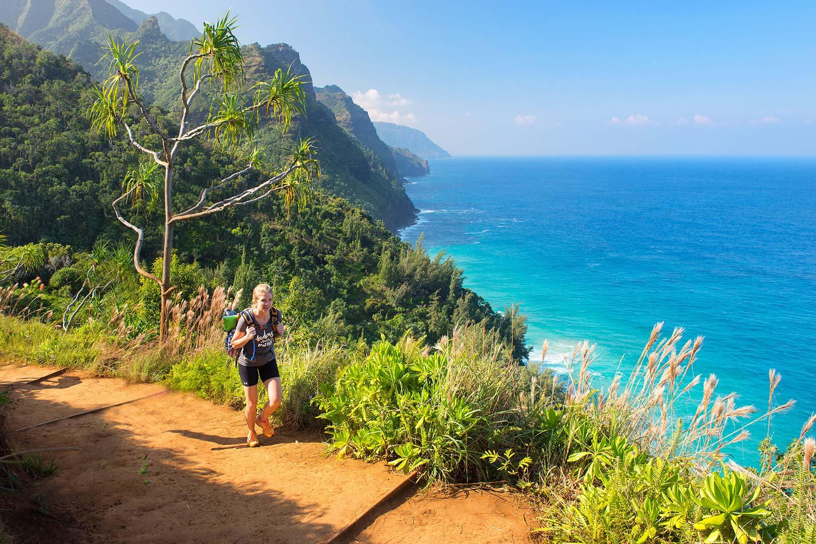 Picture of a woman hiking Kalalau Trail on the Na Pali Coast, Kauai, Hawaii