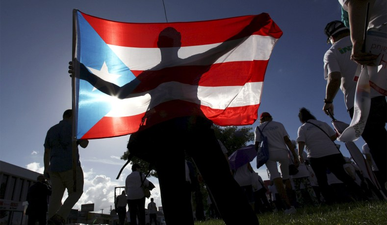 e813115f320 A protester holding a Puerto Rican flag takes part in a march to improve  healthcare benefits in San Juan