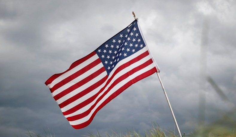 american flag outside against grey clouds