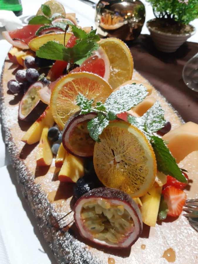 Trionfo di frutta mista con arance disidratate, menta, vaniglia e zucchero a velo