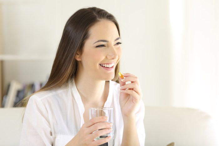woman-taking-vitamin-with-water