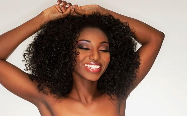 Joyful woman wearing curly hair and makeup